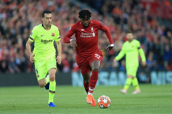 Divock Origi of Liverpool battles with Sergio Busquets of Barcelona during the UEFA Champions League Semi Final second leg match between Liverpool and FC Barcelona at Anfield on May 7, 2019 in Liverpool, England. PHOTO/ GETTY IMAGES