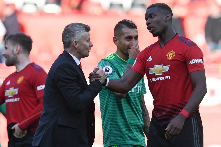 Manchester United's Norwegian manager Ole Gunnar Solskjaer (left) shakes hands with Manchester United's French midfielder Paul Pogba after the final whistle of the English Premier League football match between Manchester United and Watford at Old Trafford in Manchester, north west England, on March 30, 2019. PHOTO/AFP
