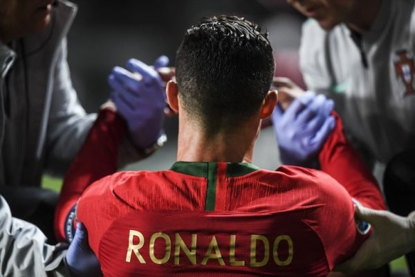 Portugal's forward Cristiano Ronaldo is attended by doctors during the Euro 2020 qualifying group B football match between Portugal and Serbia at the Luz stadium in Lisbon on March 25, 2019. PHOTO/AFP