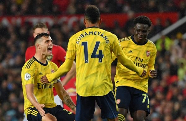 Arsenal's Gabonese striker Pierre-Emerick Aubameyang (C) celebrates with Arsenal's Swiss midfielder Granit Xhaka (L) and Arsenal's English striker Bukayo Saka (R) after scoring their first goal, decision of off-side overturned by VAR (Video Assistant referee) during the English Premier League football match between Manchester United and Arsenal at Old Trafford in Manchester, north west England, on September 30, 2019. PHOTO | AFP
