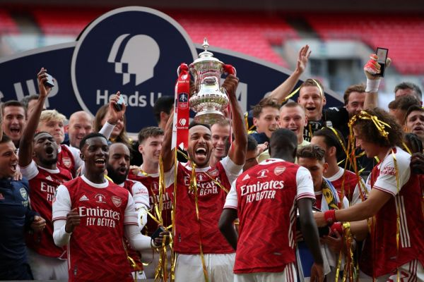 Arsenal's Gabonese striker Pierre-Emerick Aubameyang (C) holds the winner's trophy as the team celebrates victory after the English FA Cup final football match between Arsenal and Chelsea at Wembley Stadium in London, on August 1, 2020. Arsenal won the match 2-1. PHOTO | AFP