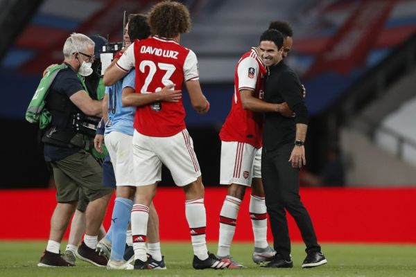 Arsenal's Spanish head coach Mikel Arteta (R) embraces Arsenal's Gabonese striker Pierre-Emerick Aubameyang (2R) at the end of the English FA Cup semi-final football match between Arsenal and Manchester City at Wembley Stadium in London, on July 18, 2020. PHOTO | AFP