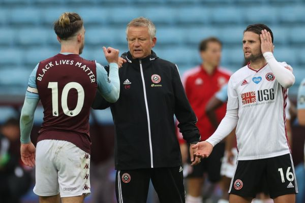Aston Villa's English midfielder Jack Grealish (L), Sheffield United's English manager Chris Wilder (2nd L) and Sheffield United's English-born Northern Irish midfielder Oliver Norwood (3rd L) tap hands after the English Premier League football match between Aston Villa and Sheffield United at Villa Park in Birmingham, central England on June 17, 2020. PHOTO | AFP