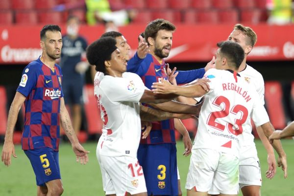 Barcelona's Spanish defender Gerard Pique (C) argues with Sevilla's Spanish defender Sergio Reguilon (R) during the Spanish league football match between Sevilla FC and FC Barcelona at the Ramon Sanchez Pizjuan stadium in Seville on June 19, 2020. PHOTO | AFP
