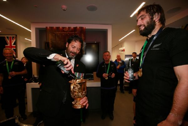 Bill Henry 'Willie' Apiata VC pours a beer into the Webb Ellis Cup with Sam Whitelock of New Zealand watching on as the New Zealand team celebrate in the dressing room after the 2015 Rugby World Cup Final match between New Zealand and Australia at Twickenham Stadium on October 31, 2015 in London, United Kingdom.PHOTO/GETTY IMAGES