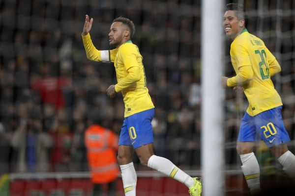 Brazil's striker Neymar (L) celebrates with Brazil's striker Roberto Firmino (R) after scoring the opening goal from the penalty spot during the international friendly football match between Brazil and Uruguay at The Emirates Stadium in London on November 16, 2018. PHOTO/AFP