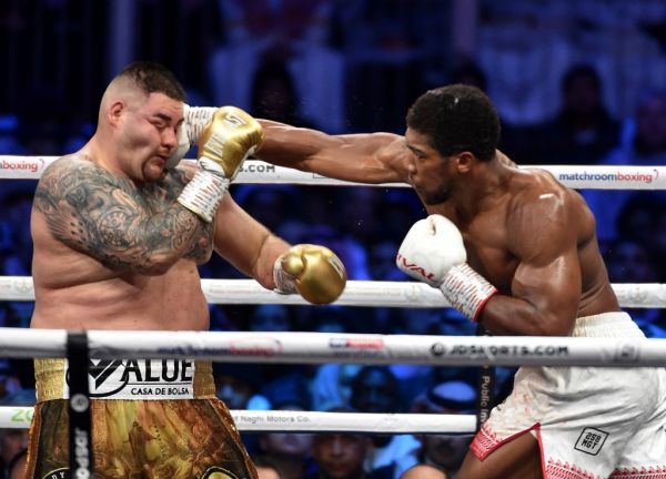 """British boxer Anthony Joshua (white trunks) competes with Mexican-American boxer Andy Ruiz Jr (golden trunks) during the heavyweight boxing match between Andy Ruiz Jr. and Anthony Joshua for the IBF, WBA, WBO and IBO titles in Diriya, near the Saudi capital on December 7, 2019. Ruiz seeks to win back the titles that he lost to Ruiz in a shock June defeat in New York in this high-profile duel , dubbed """"Clash on the Dunes"""". PHOTO 