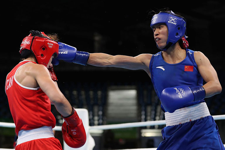 Cancan Ren of People's Republic of China throws a right on Mandy Bujold of Canada in the Women's Boxing Fly Weight (48-51kg) Quarterfinal 2 on Day 11 of the Rio 2016 Olympic Games at Riocentro on August 16, 2016 in Rio de Janeiro, Brazil. PHOTO/IOC