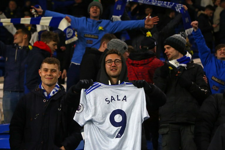 Cardiff supporters hold a shirt to honour Cardiff's Argentinian striker Emiliano Sala, whose flight disappeared from radar over the English Channel north of Guernsey, after the English Premier League football match between between Cardiff City and Bournemouth at Cardiff City Stadium in Cardiff, south Wales on February 2, 2019. PHOTO/AFP