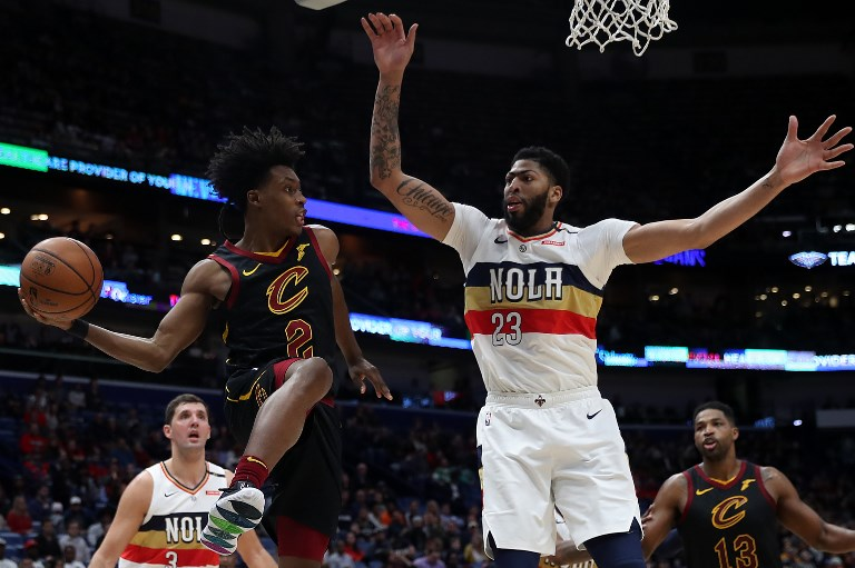 Collin Sexton (left) of the Cleveland Cavaliers passes the ball around Anthony Davis of the New Orleans Pelicans at Smoothie King Center on January 09, 2019 in New Orleans, Louisiana. PHOTO/AFP