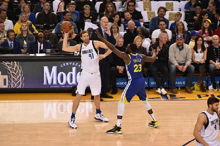 Dirk Nowitzki #41 of the Dallas Mavericks looks to pass against Draymond Green #23 of the Golden State Warriors on March 23, 2019 at ORACLE Arena in Oakland, California. PHOTO/GettyImages