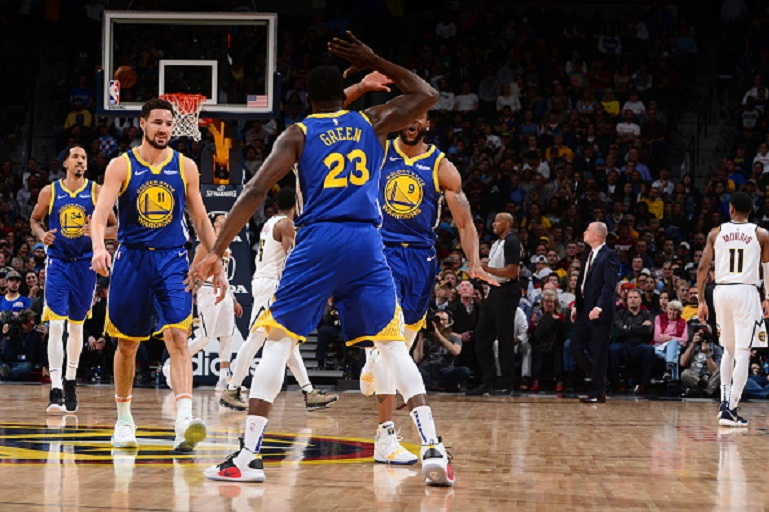 Draymond Green #23 of the Golden State Warriors hi-fives teammates during the game against the Denver Nuggets on January 15, 2019 at the Pepsi Center in Denver, Colorado. PHOTO/GettyImages