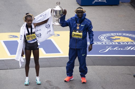 Ethopian Worknesh Degefa(L), and Kenyan Lawrence Cherono, celebrate together after they won the Women's Elite, and Men's Elite races respectfully at the 123rd Boston Marathon on April 15, 2019 in Boston, Massachusetts. PHOTO/AFP