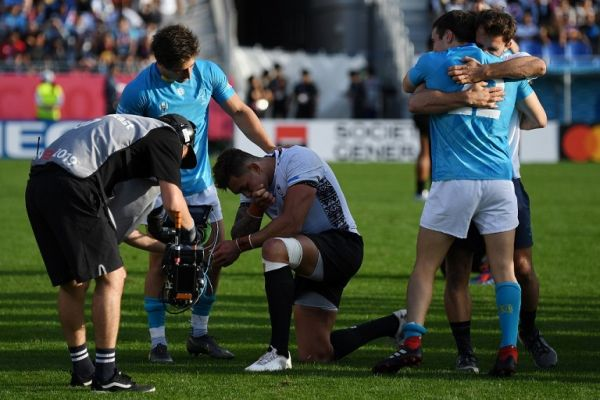 Fiji's centre Jale Vatubua (C) reacts after losing as Uruguay's players celebrate winning the Japan 2019 Rugby World Cup Pool D match between Fiji and Uruguay at the Kamaishi Recovery Memorial Stadium in Kamaishi on September 25, 2019. PHOTO | AFP