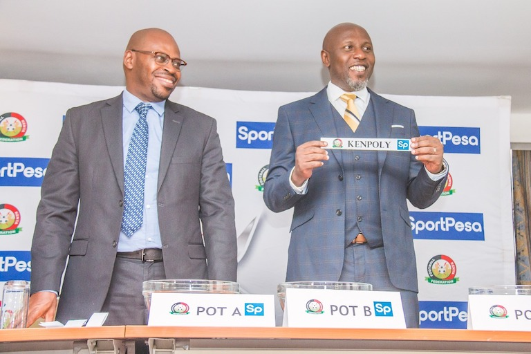 Football Kenya Federation chief executive, Robert Muthomi (left) watches on as SportPesa Chief Marketing Officer, Kelvin Twissa, pulls Kenpoly out of the pot to play Gor Mahia during the launch and draw of the 2019 FKF SportPesa Shield Cup tournament in Nairobi on March 7, 2019. PHOTO/SPN