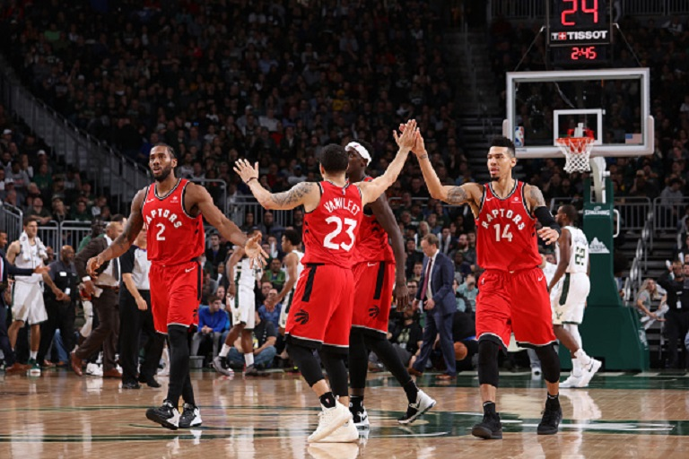 Fred VanVleet #23 of the Toronto Raptors hi fives teammates during the game against the Milwaukee Bucks on January 5, 2019 at the Fiserv Forum Center in Milwaukee, Wisconsin. PHOTO/GettyImages