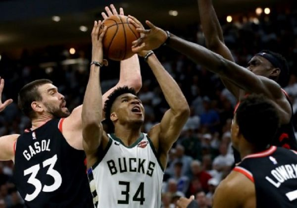 Giannis Antetokounmpo #34 of the Milwaukee Bucks attempts a shot while being guarded by Marc Gasol #33 and Pascal Siakam #43 of the Toronto Raptors in the fourth quarter in Game One of the Eastern Conference Finals of the 2019 NBA Playoffs at the Fiserv Forum on May 15, 2019 in Milwaukee, Wisconsin. PHOTO/ AFP