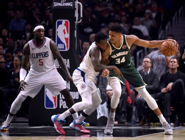 Giannis Antetokounmpo #34 of the Milwaukee Bucks back down Patrick Beverley #21 of the LA Clippers as Montrezl Harrell #5 looks on during the first half at Staples Center on November 06, 2019 in Los Angeles, California. PHOTO | AFP
