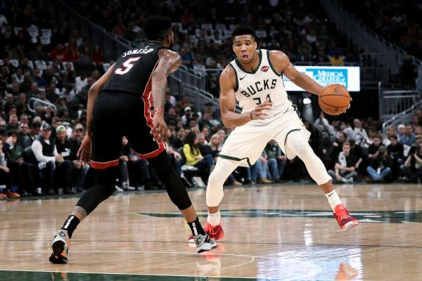 Giannis Antetokounmpo #34 of the Milwaukee Bucks dribbles the ball while being guarded by Derrick Jones Jr. #5 of the Miami Heat in the second quarter at the Fiserv Forum on October 26, 2019 in Milwaukee, Wisconsin. PHOTO | AFP