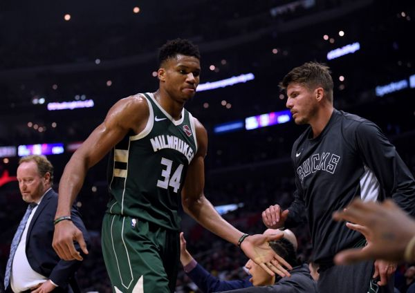 Giannis Antetokounmpo #34 of the Milwaukee Bucks reacts as he leaves the game with two fouls past Kyle Korver #26 during the first half at Staples Center on November 06, 2019 in Los Angeles, California. PHOTO | AFP