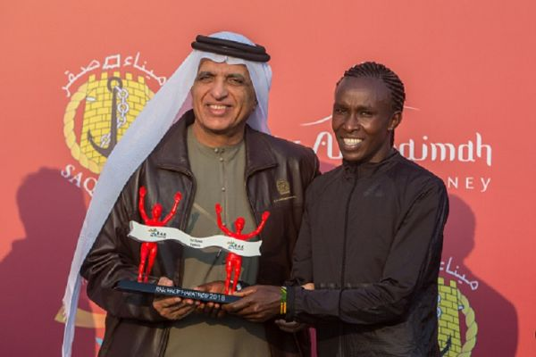 His Highness Sheikh Saud Bin Saqr Al Qasimi hands over the winner's trophy to Fancy Chemutai from Kenya (Right) who won the woman's RAK Half Marathon in a time of 1:04:53. PHOTO/ GETTY IMAGES