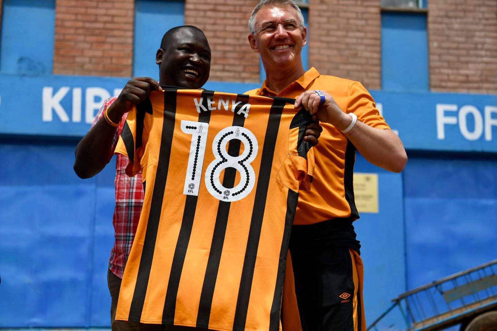 Hull City FC manager, Nigel Adkins present a branded shirt to Shofco FC founder, Kennedy Odede, when the team visited sprawling Kibera slum in Nairobi, Kenya, in May, 2018.PHOTO/SPN