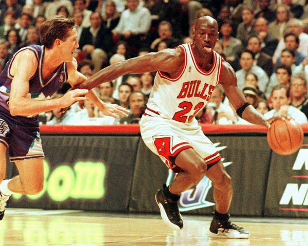 """In this file photo taken on June 4, 1997 Chicago Bulls player Michael Jordan sticks out his tongue as he goes past Jeff Hornacek of the Utah Jazz during game two of the NBA Finals at the United Center in Chicago, IL. The immense global success of the documentary """"The Last Dance"""" amid the coronavirus lockdown has boosted sales of collectibles related to NBA icon Michael Jordan, some of which are trading in the hundreds of thousands of dollars. PHOTO   AFP"""
