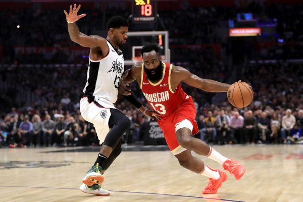 In this file photo taken on November 22, 2019 James Harden #13 of the Houston Rockets dribbles past Paul George #13 of the Los Angeles Clippers during the first half of a game at Staples Center in Los Angeles, California. James Harden tied Michael Jordan for the third most 60-point performances in NBA history on November 30, 2019 as the Houston Rockets blasted the last-place Atlanta Hawks 158-111.PHOTO | AFP