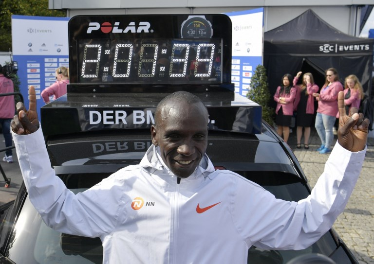 In this file photo taken on September 16, 2018 Kenya's Eliud Kipchoge stands in front of a clock displaying his time after winning the Berlin Marathon setting a new world record with 2h01m39s in Berlin. PHOTO/AFP