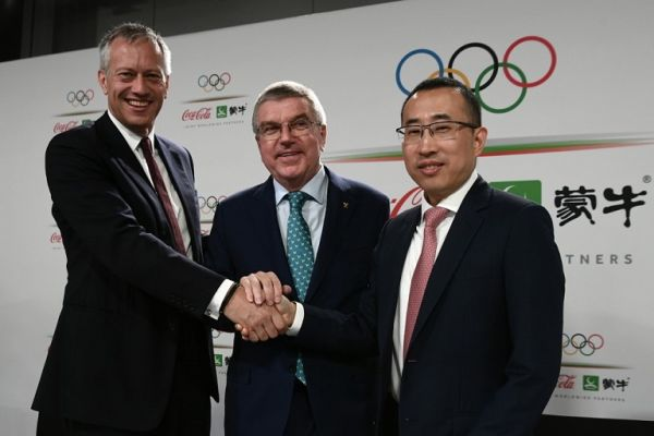 International Olympic Committee (IOC) president Thomas Bach (C) shakes hands with Coca-Cola President and CEO James Quincey (L) and China Mengniu Dairy CEO and Executive Director Jeffrey Minfang as they pose for photos during a press conference as part of the 134th Session of the International Olympic Committee (IOC) at the SwissTech Convention Centre in Lausanne, on June 24, 2019. PHOTO | AFP