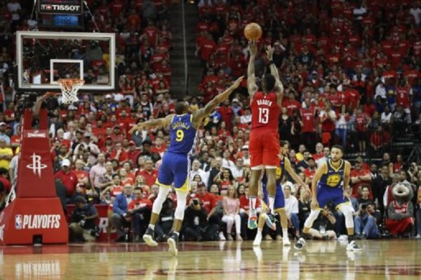 James Harden #13 of the Houston Rockets takes a three point shot defended by Andre Iguodala #9 of the Golden State Warriors in overtime during Game Three of the Second Round of the 2019 NBA Western Conference Playoffs at Toyota Center on May 4, 2019 in Houston, Texas. PHOTO/AFP