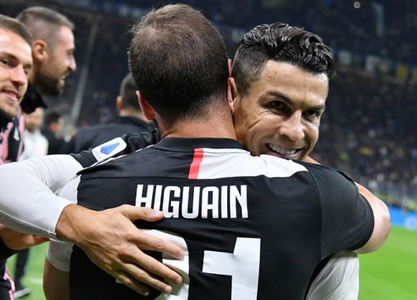 Juventus' Argentinian forward Gonzalo Higuain (Front) embraces Juventus' Portuguese forward Cristiano Ronaldo after scoring during the Italian Serie A football match Inter vs Juventus on October 6, 2019 at the San Siro stadium in Milan. PHOTO | AFP