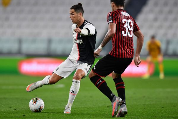 Juventus' Portuguese forward Cristiano Ronaldo challenges AC Milan's Brazilian midfielder Lucas Paqueta during the Italian Cup (Coppa Italia) semi-final second leg football match Juventus vs AC Milan on June 12, 2020 at the Allianz stadium in Turin, the first to be played in Italy since March 9 and the lockdown aimed at curbing the spread of the COVID-19 infection, caused by the novel coronavirus. PHOTO | AFP