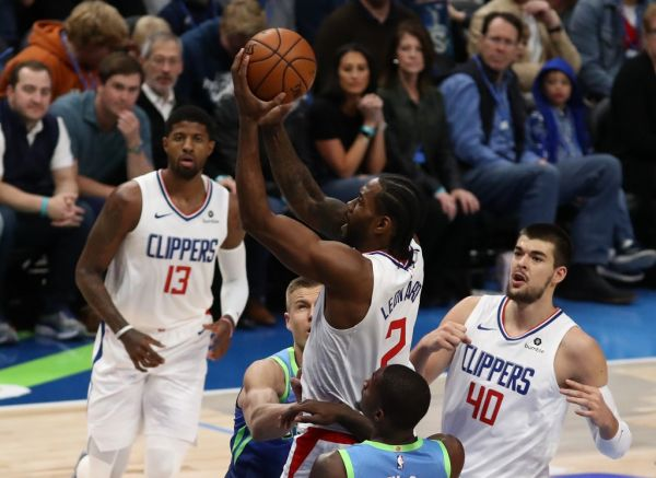 Kawhi Leonard #2 of the Los Angeles Clippers takes a shot against Kristaps Porzingis #6 and Dorian Finney-Smith #10 of the Dallas Mavericks at American Airlines Center on November 26, 2019 in Dallas, Texas. PHOTO | AFP