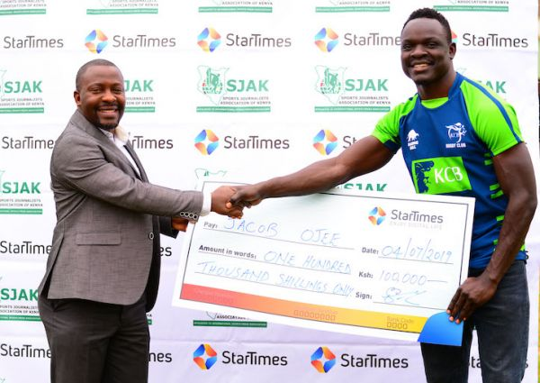 KCB RFC winger, Jacob Ojee (right) receives his KSh100,000 dummy cheque from Regional Director of Marketing, StarTimes Aldrine Nsubuga during the presentation ceremony of Sports Personality of the Month for May in Nairobi on Thursday, July 4, 2019. PHOTO/Courtesy