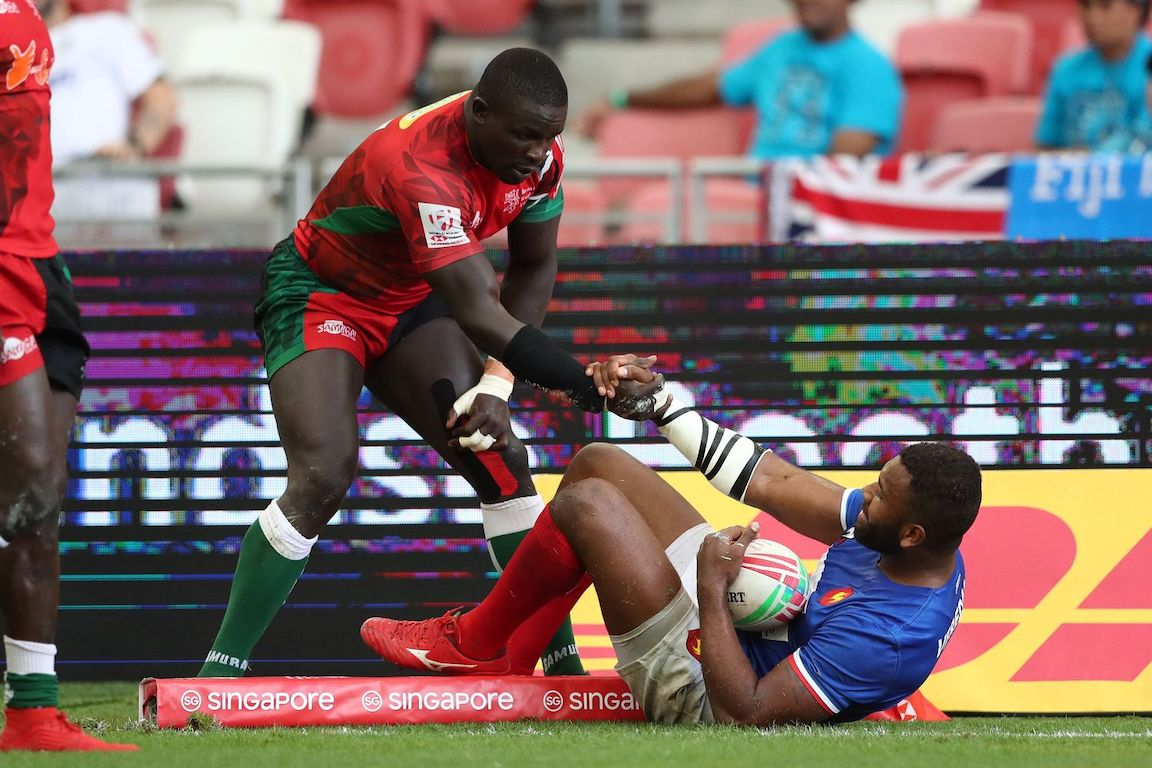 Kenya's Bush Mwale helps France's Tavite Veredamu to get up from the floor on day two of the HSBC World Rugby Sevens Series in Singapore on 14 April, 2019. PHOTO/Mike Lee/KLC fotos for World Rugby
