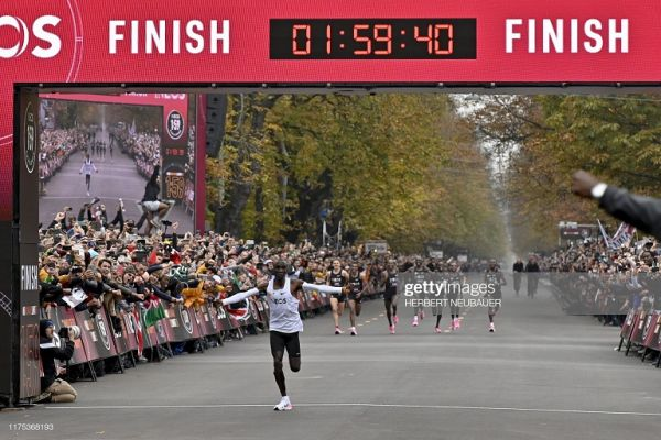 Kenya's Eliud Kipchoge (white jersey) celebrates as he crosses the finish line at the end of his attempt to bust the mythical two-hour barrier for the marathon on October 12 2019 in Vienna. PHOTO/ GETTY IMAGES
