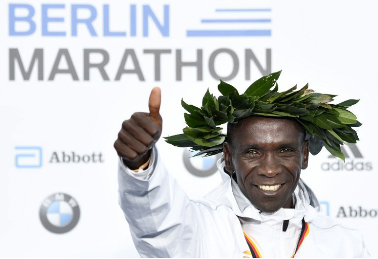 Kenya's Eliud Kipchoge celebrates on the podium during the winner's ceremony after winning the Berlin Marathon setting a new world record on September 16, 2018 in Berlin. PHOTO/AFP