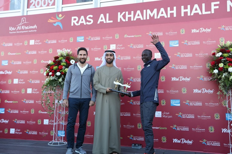 Kenya's Stephen Kiprotich (right) receives his trophy after winning the 2019 Ras-Al-Khaimah Half Marathon in the UAE on Friday, February 8, 2019. PHOTO/Organisers