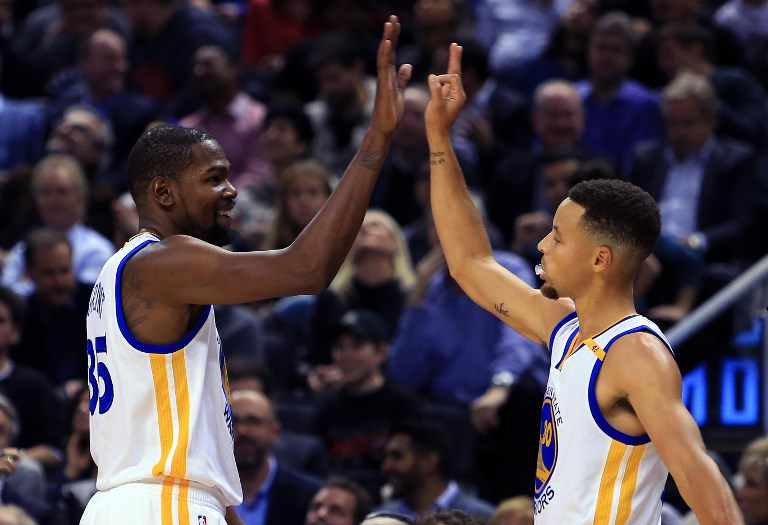 Kevin Durant #35 and Steph Curry #30 of the Golden State Warriors high five during the first half of an NBA game against the Toronto Raptors at Air Canada Centre on November 16, 2016 in Toronto, Canada. PHOTO/AFP