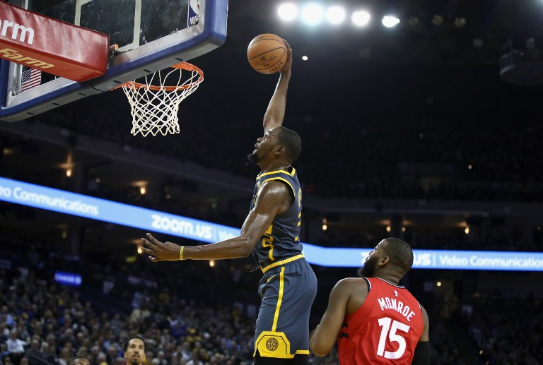 Kevin Durant of the Golden State Warriors dunks over Greg Monroe of the Toronto Raptors at ORACLE Arena on December 12, 2018 in Oakland, California. PHOTO/AFP