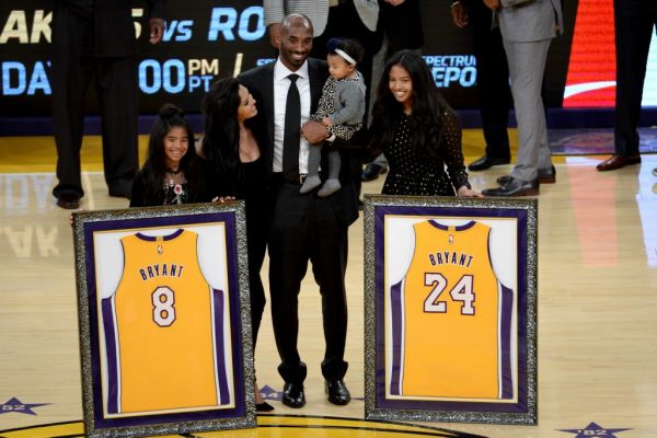 Kobe Bryant poses with his family at halftime after both his #8 and #24 Los Angeles Lakers jerseys are retired at Staples Center on December 18, 2017 in Los Angeles, California. PHOTO | AFP