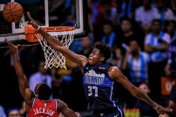 Kostas Antetokounmpo of Dallas Mavericks, right, jumps to block a shot by Demetrius Jackson of Philadelphia 76ers during the Shenzhen match of the NBA China Games in Shenzhen city, south China's Guangdong province, 8 October 2018.PHOTO/AFP