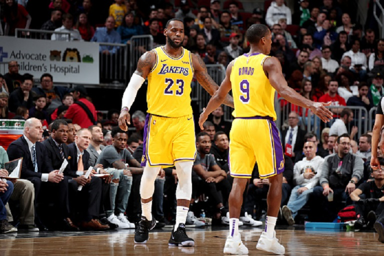 LeBron James #23 and Rajon Rondo #9 of the Los Angeles Lakers high five during the game against the Chicago Bulls on March 12, 2019 at the United Center in Chicago, Illinois. PHOTO/GettyImages