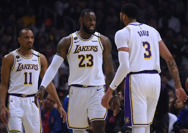 LeBron James #23 of the Los Angeles Lakers reacts between Avery Bradley #11 and Anthony Davis #3 during a 112-103 win over the LA Clippers at Staples Center on March 08, 2020 in Los Angeles, California. PHOTO | AFP