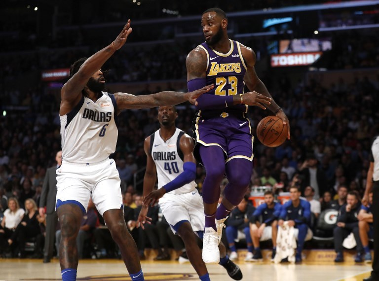 LeBron James (right) of the Los Angeles Lakers passes the ball past DeAndre Jordan (6) and Harrison Barnes (40) of the Dallas Mavericks during the second half of a game at Staples Center on October 31, 2018 in Los Angeles, California. PHOTO/AFP