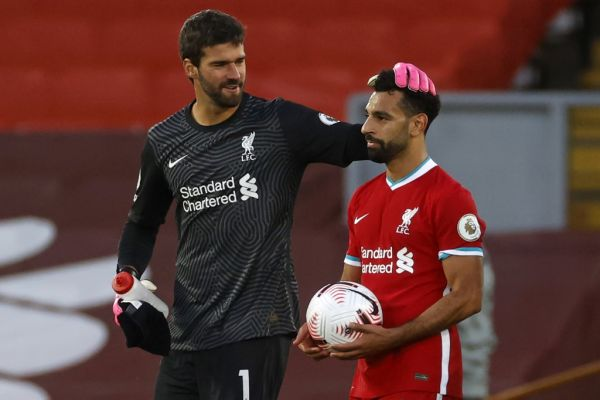 Liverpool's Egyptian midfielder Mohamed Salah takes the match ball as he walks off with Liverpool's Brazilian goalkeeper Alisson Becker after the English Premier League football match between Liverpool and Leeds United at Anfield in Liverpool, north west England on September 12, 2020. Liverpool won the game 4-3. PHOTO | AFP