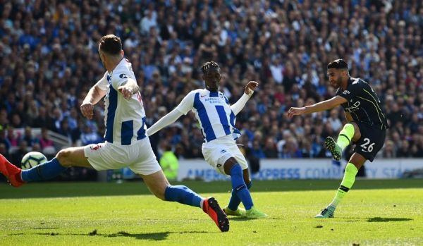 Manchester City's Algerian midfielder Riyad Mahrez (R) scores their third goal during the English Premier League football match between Brighton and Hove Albion and Manchester City at the American Express Community Stadium in Brighton, southern England on May 12, 2019. PHOTO/AFP