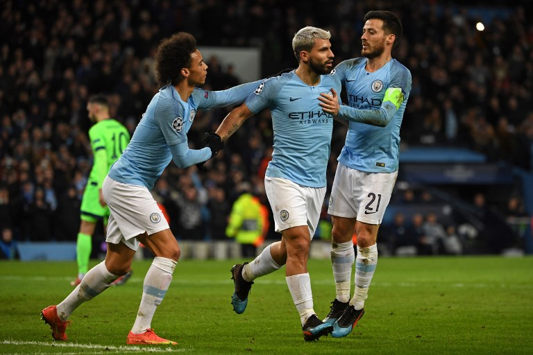 Manchester City's Argentinian striker Sergio Aguero (C) celebrates with Manchester City's German midfielder Leroy Sane (L) and Manchester City's Spanish midfielder David Silva (R) after scoring the opening goal from the penalty spot during the UEFA Champions League round of 16 second leg football match between Manchester City and Schalke 04 at the Etihad Stadium in Manchester, north west England, on March 12, 2019. PHOTO/ AFP