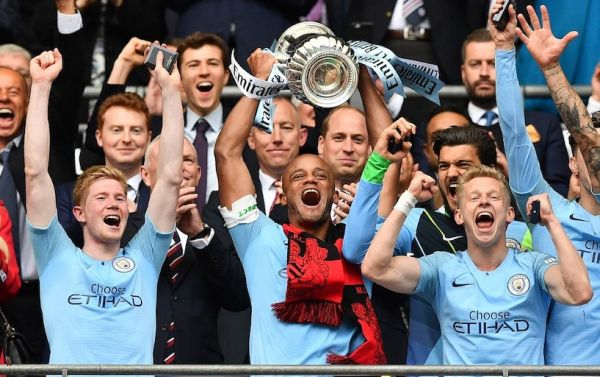 Manchester City's Belgian captain Vincent Kompany (C) lifts the winner's trophy as the players celebrate victory after the English FA Cup final football match between Manchester City and Watford at Wembley Stadium in London, on May 18, 2019. Manchester City beat Watford 6-0 at Wembley to claim the FA Cup. PHOTO/AFP